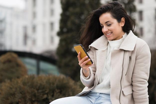 Smiley kobieta patrzeje telefon outdoors