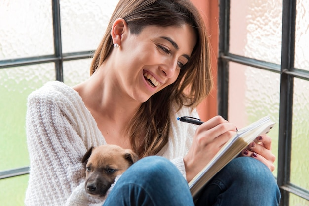 Smiley kobieta pisze na notebooku