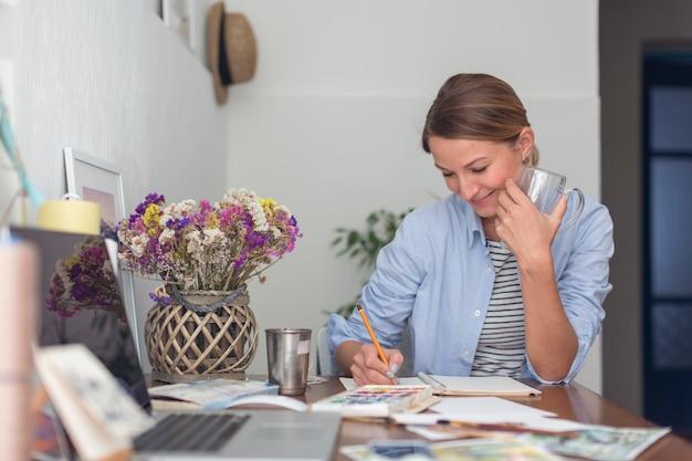 Smiley kobieta pisze przy biurku w notatniku