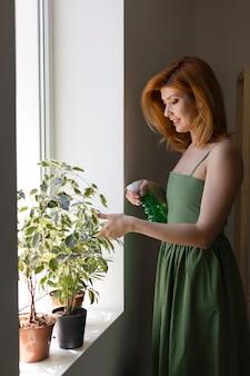 Smiley kobieta podlewanie roślin średni strzał