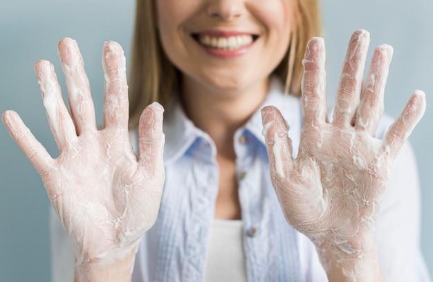 Smiley kobieta pokazuje jej ręki z mydłem i pianą