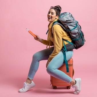 Smiley kobieta pozuje na jej bagażu