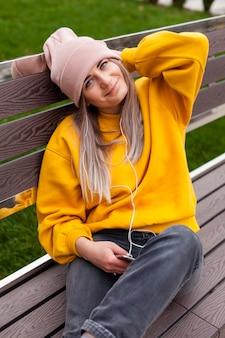 Smiley kobieta pozuje na ławce podczas gdy będący ubranym czapka