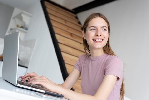 Smiley kobieta pracuje na jej laptopie w domu