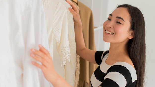 Smiley kobieta próbuje na ubrania