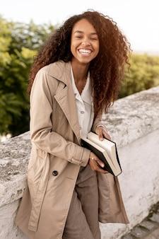 Smiley kobieta relaksujący poza z książką