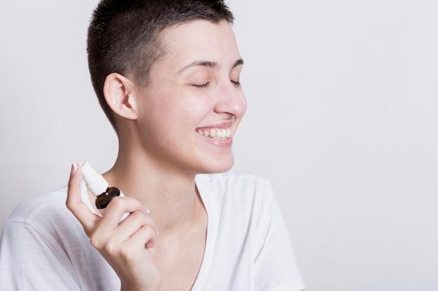 Smiley kobieta rozpylania produktu do pielęgnacji twarzy
