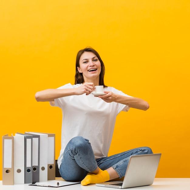 Smiley kobieta siedzi na biurku i ciesząc się jej filiżankę kawy