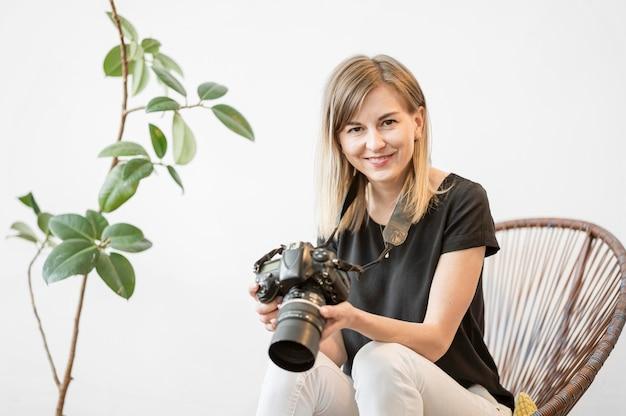 Smiley kobieta siedzi na krześle ze zdjęciem aparatu