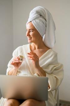 Smiley kobieta stosuje śmietankę na jej twarzy w domu