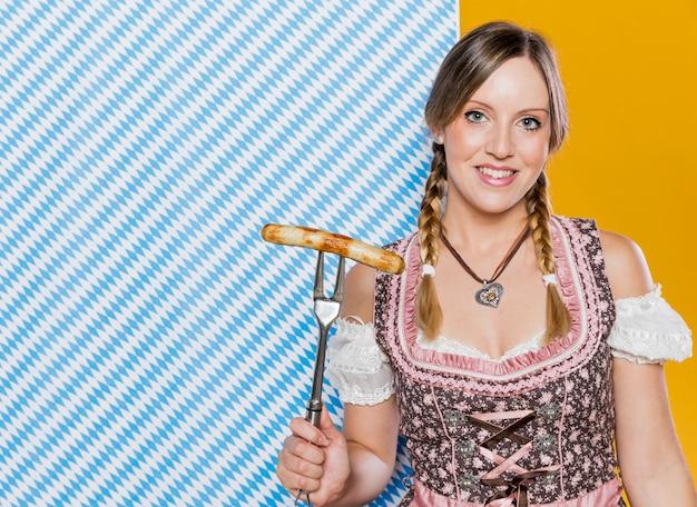 Smiley kobieta trzyma kiełbasę z grilla