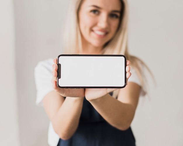 Smiley kobieta trzyma telefon z makiety
