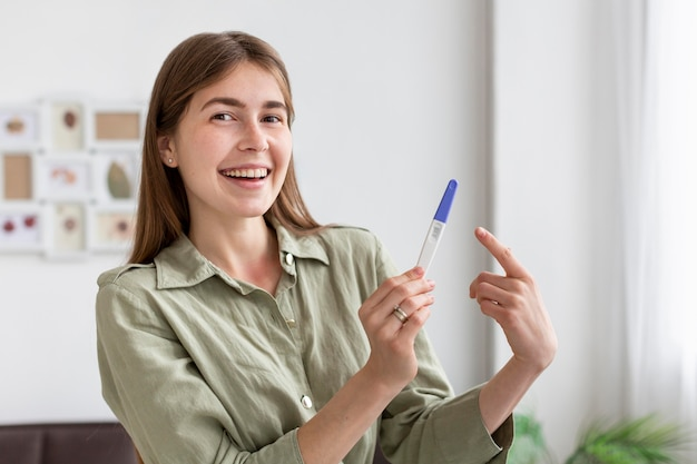 Smiley kobieta trzyma test ciążowy
