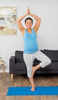 Smiley kobieta w ciąży joga szkolenia w domu na macie