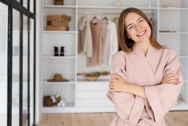 Smiley kobieta w różowej szacie patrząc na kamery
