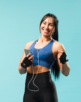 Smiley kobieta w stroju siłowni muzyki w słuchawkach