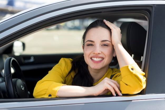 Smiley kobieta w żółtej koszuli siedzi w samochodzie