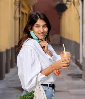 Smiley kobieta z maską i torby na zakupy