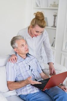 Smiley kobieta z zaskoczony mężczyzna i laptop