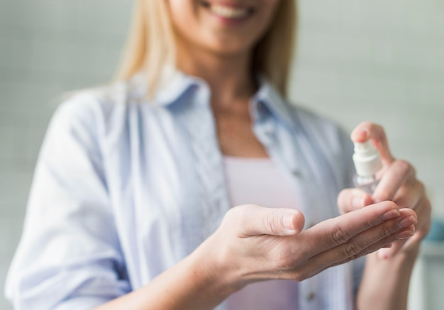 Smiley kobieta za pomocą dezynfekcji rąk
