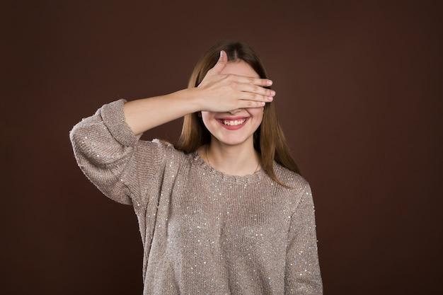 Smiley kobieta zasłaniając oczy rękami na brązowej ścianie