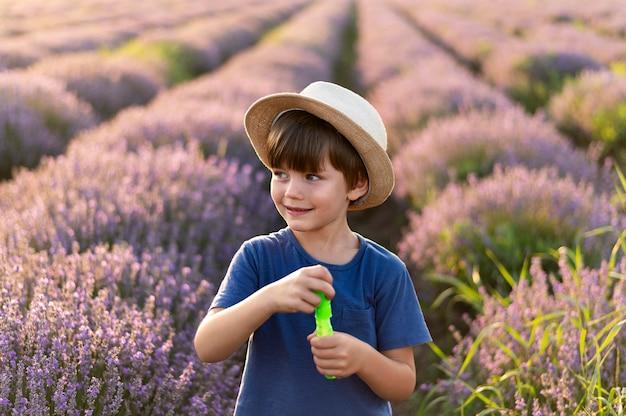 Smiley mały chłopiec w dziedzinie kwiatów