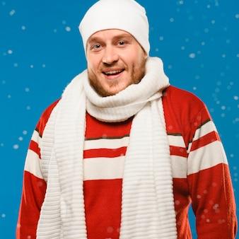 Smiley mężczyzna patrzeje kamerę podczas gdy będący ubranym zimę odziewa