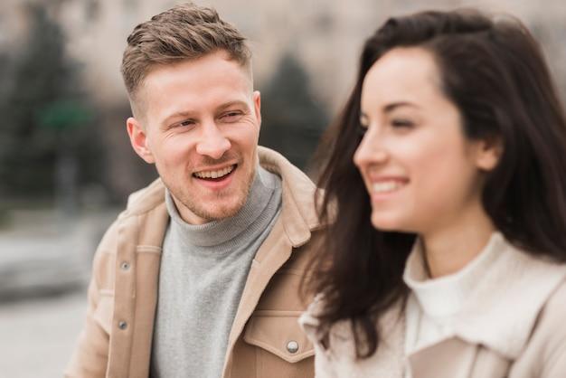 Smiley mężczyzna rozmawia z kobietą na zewnątrz