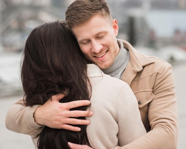 Smiley mężczyzna trzyma kobiety na zewnątrz