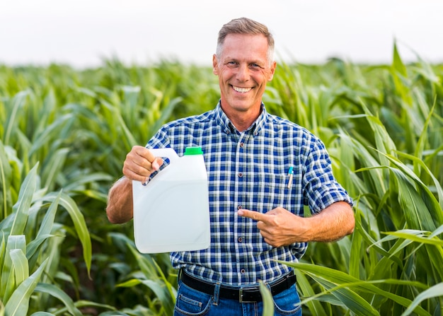 Smiley mężczyzna wskazuje przy insektycydu kanisterem