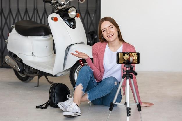 Smiley młoda blogerka nagrywająca się siedząca obok motocykla