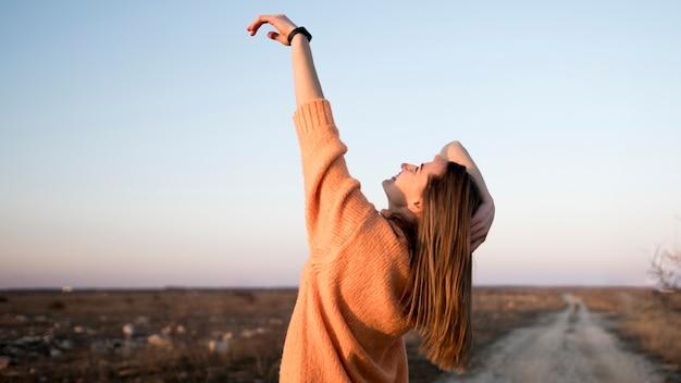 Smiley młoda dziewczyna na drodze z ręką w powietrzu