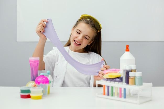 Smiley młoda dziewczyna naukowiec robi szlam