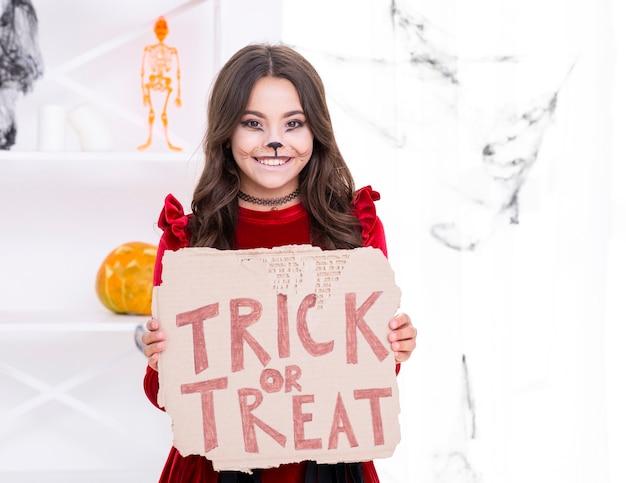 Smiley młoda dziewczyna trzyma znak cukierek albo psikus