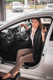 Smiley młoda kobieta bada samochód
