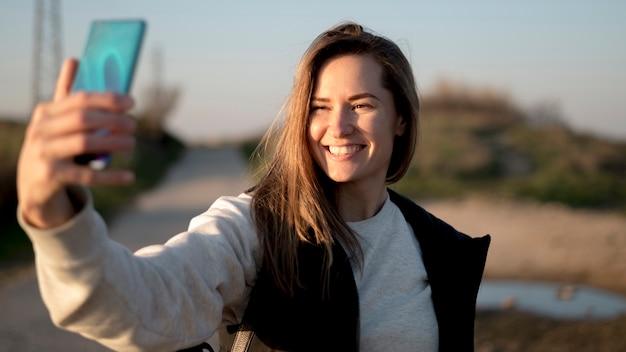 Smiley młoda kobieta bierze fotografię