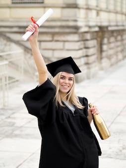 Smiley młoda kobieta ma na sobie suknię ukończenia szkoły