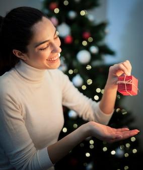Smiley młoda kobieta trzyma małego prezent