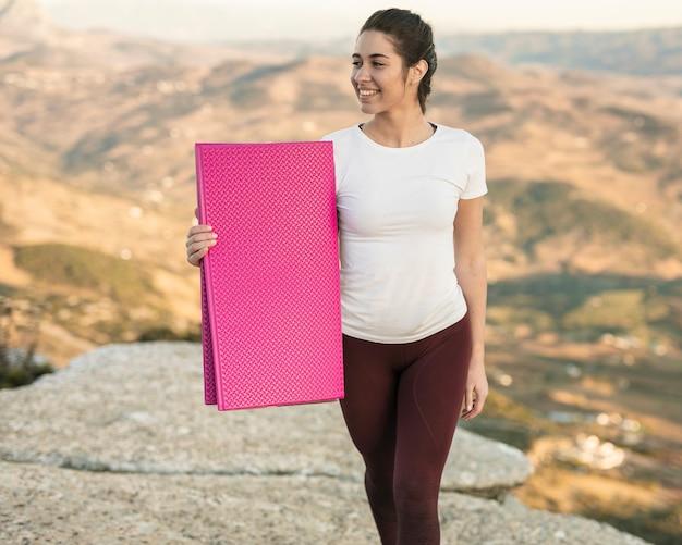 Smiley młoda kobieta trzyma matę do jogi