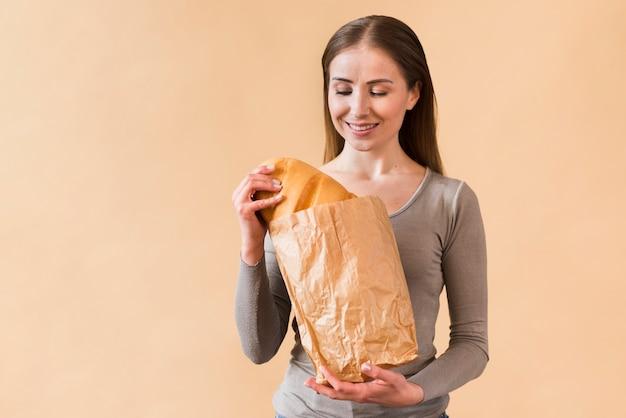Smiley młoda kobieta trzyma papierową torbę z chlebem