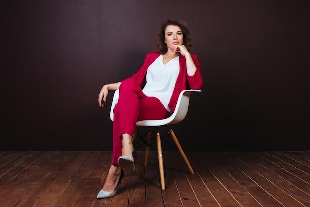 Smiley młody bizneswomanu obsiadanie na biurowym krześle nad ciemnym tłem