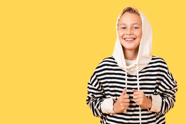 Smiley młody chłopak ubrany w bluzę z kapturem