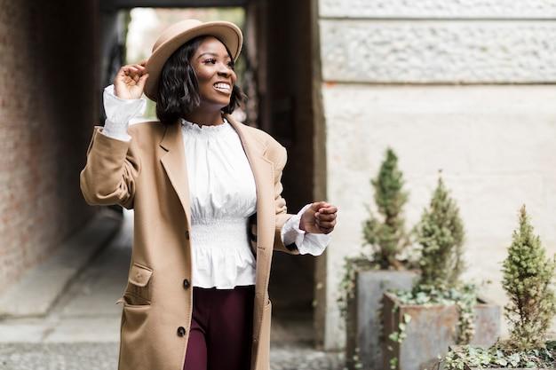 Smiley modna kobieta pozuje podczas gdy trzymający jej kapelusz
