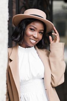 Smiley modna kobieta pozuje podczas gdy trzymający jej kapeluszowego outside