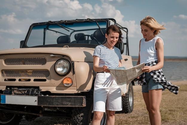 Smiley przyjaciele podróżujący samochodem i sprawdzający mapę