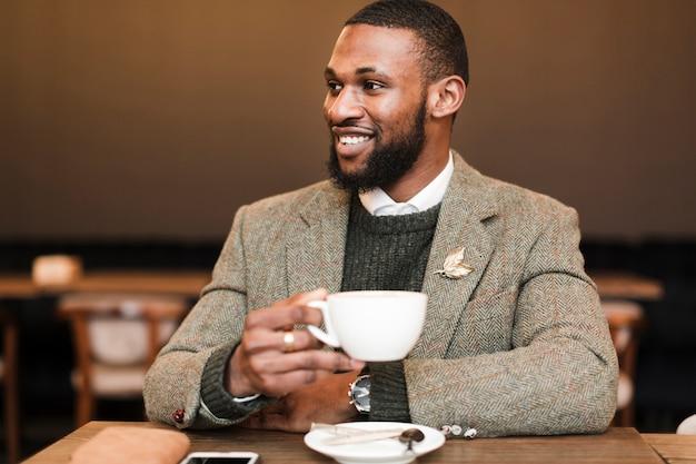Smiley przystojny mężczyzna trzyma kubek z kawą