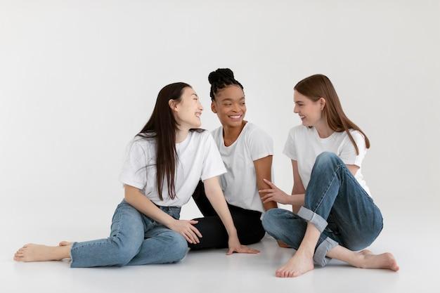 Smiley różnorodne kobiety stwarzające pełne ujęcie