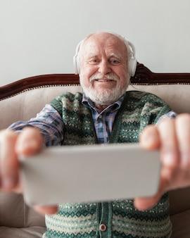 Smiley senior ogląda muzykę wideo na telefonie komórkowym