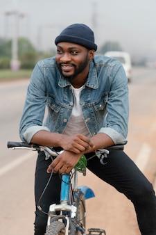 Smiley smiley mężczyzna pozuje z rowerem