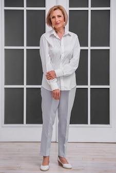 Smiley starsza kobieta jest ubranym białą koszula